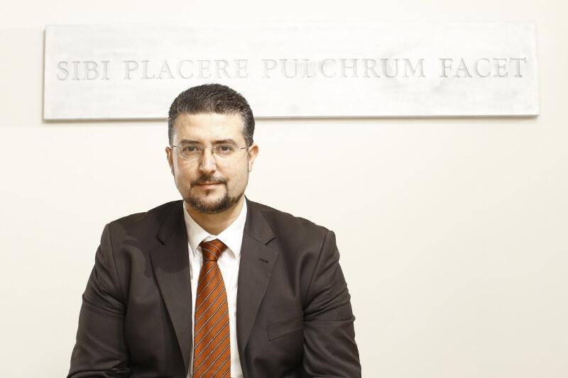 Der Plastische Chirurg Georgios Hristopoulos neben dem Klinikmotto